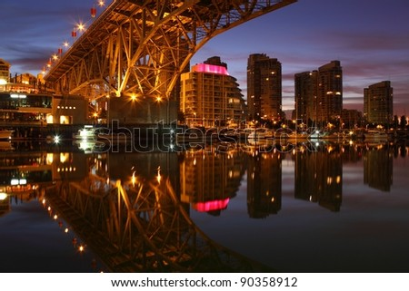 The Vancouver cityscape at dawn from Granville Island and the underside of the Granville Street Bridge crossing over the still waters of False Creek. - stock photo