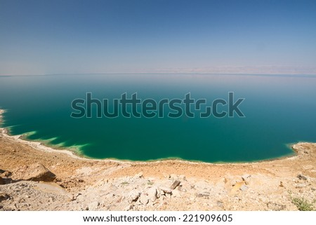 The vast, green expanse of the waters of the land-locked Dead Sea in Jordan, with a view to the Israeli side. - stock photo
