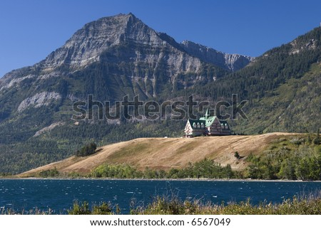 The venerable Prince of Wales Hotel overlooks Waterton Lake, backed by the Rocky Mountains. - stock photo