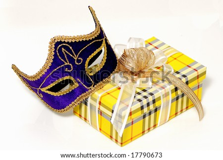 The Venetian mask with a celebratory gift on a light background - stock photo