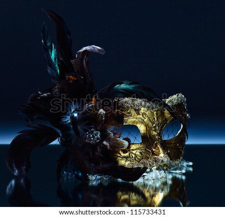 The Venetian mask with feather on a mirror table - stock photo