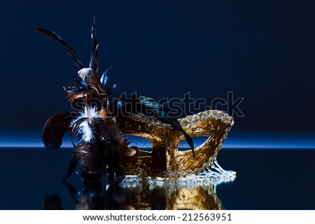 The Venetian mask with feather on  mirror table - stock photo