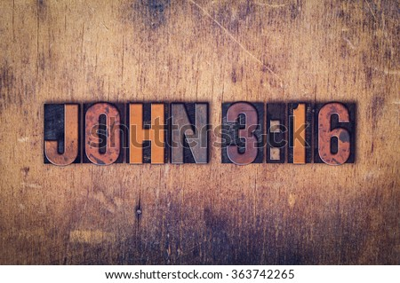 """The verse """"John 316"""" written in dirty vintage letterpress type on a aged wooden background. - stock photo"""
