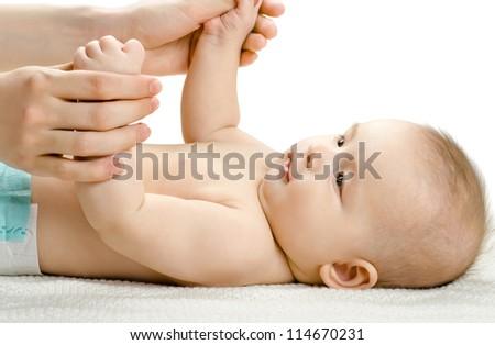 the very beautiful fun little baby make massage,  lie on light bedding - stock photo