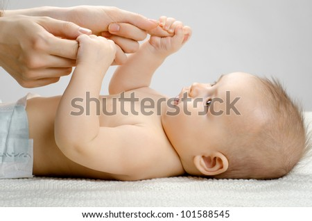 the very  beautiful  little baby with hands mother  , close face,  on grey background - stock photo