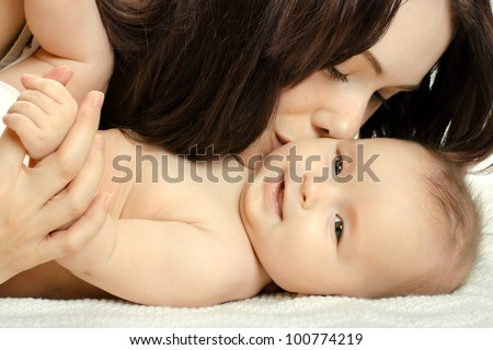 the very  beautiful  little baby with  mother  , close face,  on white background, isolated - stock photo