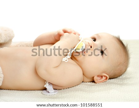 the very  beautiful  little baby with pacifier, lie on white background, isolated - stock photo