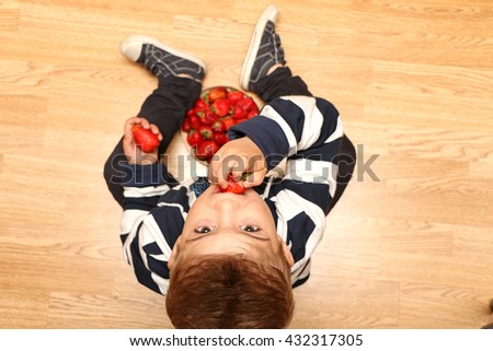 The very handsome, cute and clever boy dressed in classical style clothes and taste strawberries - stock photo