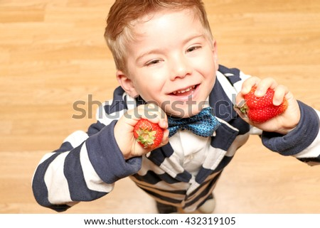 The very handsome, cute and clever boy dressed in classical style clothes looking up and holding a strawberry. - stock photo