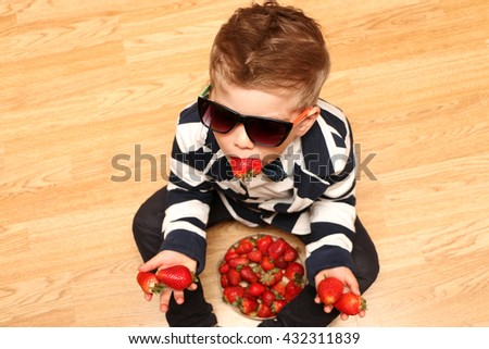 The very handsome, cute and clever boy dressed in classical style clothes showing tongue holding a strawberry - stock photo