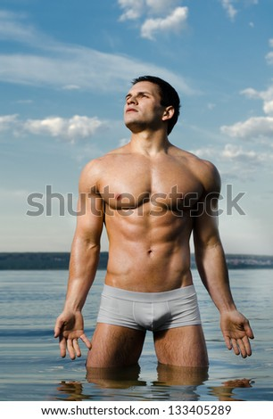 the very muscular handsome sexy guy in water, on  sky  background - stock photo