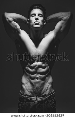 The very muscular handsome sexy guy on grey background, naked torso, black-and-white.Low light.