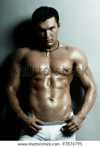 the very muscular handsome sexy guy on grey background, strict look - stock photo