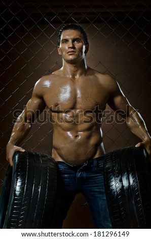 the very muscular handsome sexy guy with rubber-tire,  on  netting  steel fence background - stock photo