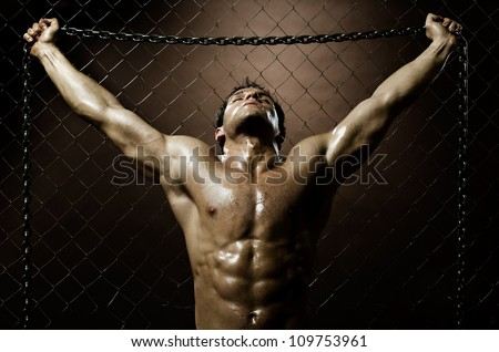 the very muscular handsome weary sexy guy ,  on  netting   steel fence with steel chain - stock photo