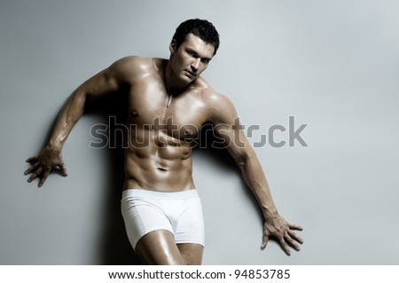the very muscular  undressed handsome sexy guy on grey background - stock photo
