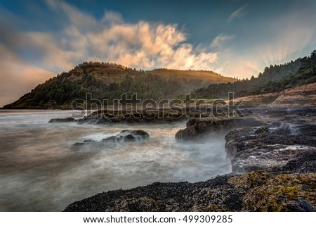 The very scenic Cape Perpetua on the Oregon Coast. Long exposure of waves crashing on the shore at sunrise.