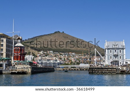 The Victoria and Alfred Waterfront in Cape Town South Africa with the historic Clock Tower on the left and Signal Hill in the background - stock photo