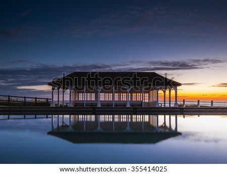 The Victorian shelter reflecting in the boating lake at Sherringham. - stock photo