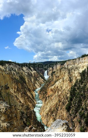 The view at Artist Point shows Lower Falls and an expanse of the Yellowstone River.  Rugged and steep canyon walls provide view of The Grand Canyon of the Yellowstone. - stock photo