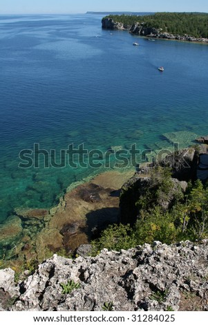 The view from a top the cliffs at Georgian Bay in  Bruce Penisula National Park in Ontario, Canada.  Featuring a bunch of boats. - stock photo