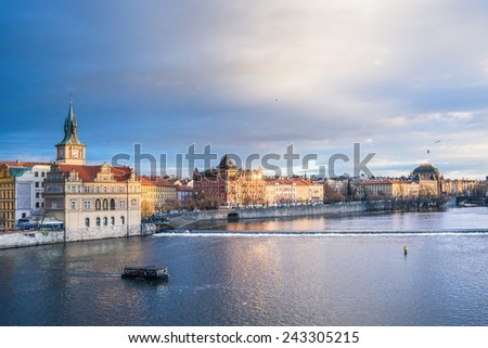 The view from the Charles bridge over the Vltava river, Smetana embankment and dramatic sky on a winter day. Prague, Czech Republic, Central Europe - stock photo