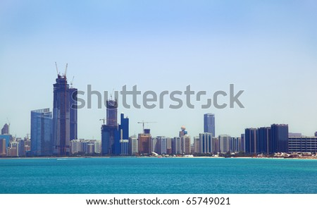 The view from the sea of the buildings and skyscrapers in Abu Dhabi downtown. - stock photo