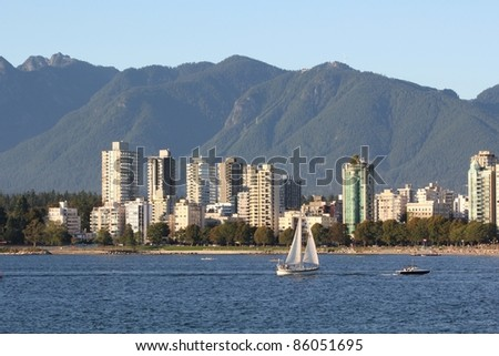 The view, in the early evening, across English Bay, the apartments of the West End, and the North Shore Mountains in Vancouver, British Columbia, Canada. - stock photo