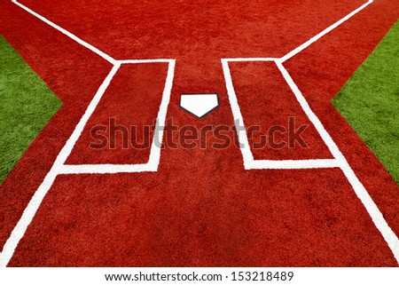 The view is at home plate looking at the batter boxes with artificial turf at a school softball field. The bright colors of the artificial turf are a high contrast to a normal playing field. - stock photo