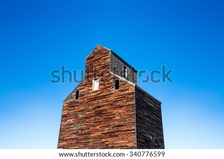 The view looking up the side of an old wooden grain elevator on the western countryside. - stock photo