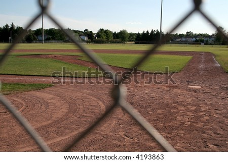 The view of a ball diamond from behind the fench. - stock photo