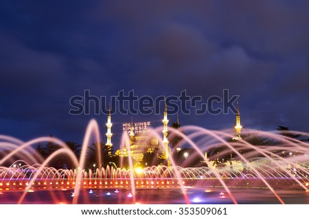 """The view of Blue mosque throught the fountain water in the evening illumination during the holy month of Ramadan, Istanbul, Turkey. Text translation: """"No one should be orphaned"""" - stock photo"""