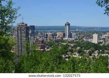 The view of downtown Hamilton with some high rises and a park in the foreground, and the lake Ontario in the background, from the mountain. - stock photo