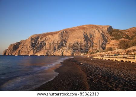 The view of Mesa Vouna Mountain from Kamari Beach in morning. - stock photo