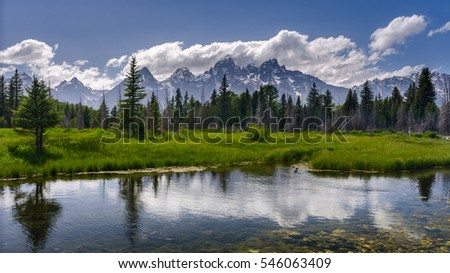 The view of the Grand Tetons range from the Schwabacher Landing under midday sun with clouds reflecting on the Teton river