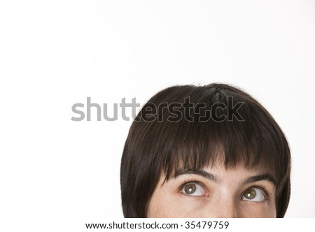 The view of the top portion of a brunette woman's head.  She is glancing upward. Horizontally framed shot.