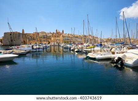 The view of yachts moored in the harbor in Dockyard creek between Senglea and Birgu  with Senglea peninsular on background. Malta - stock photo