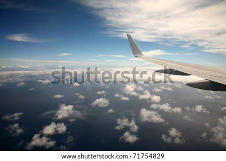 the view out the window of an airplane on the way to Maui Hawaii at 30,000 feet in the air over the pacific ocean - stock photo