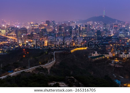 The view over downtown Seoul at dusk from atop Mount Inwangsan. - stock photo