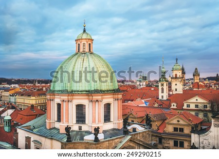 The view over Saint Francis of Assisi church and red roofs of Stare Mesto district in Prague, Czech Republic, from the view point on top of the tower of the Charles bridge on a cloudy winter evening   - stock photo