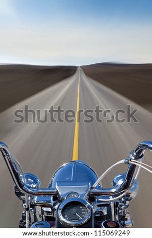 The view over the handlebars of a speeding motorcycle as it races along a deserted highway. - stock photo