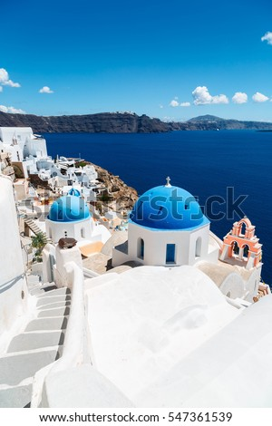 The view with traditional beautiful church over the village of Oia at the Island Santorini, Greece