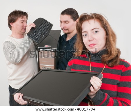 The vigorous company from three persons with the new computer. - stock photo