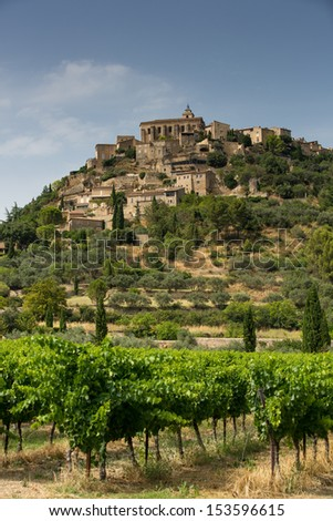 The village of Gordes with grape vines in the foreground - stock photo