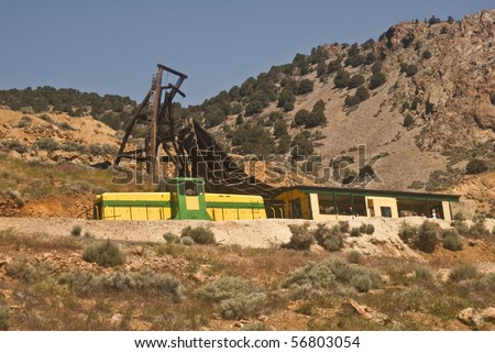 The vintage Virginia and Truckee railway in Nevada that runs tourists between Virginia City and Gold Hill ( a ghost town) with the ruins of old mining equipment in the background - stock photo
