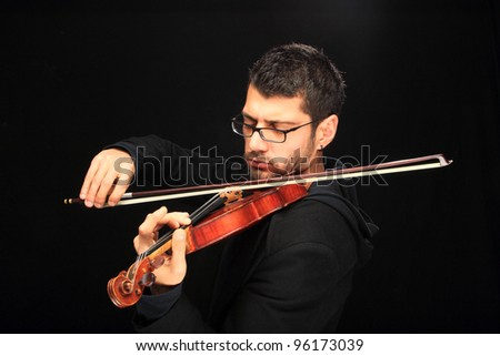 the violinist: Musician playing violin on dark background - stock photo