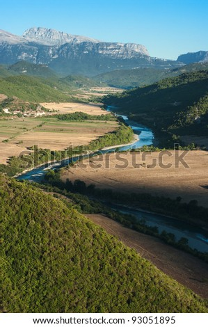 the Vjosa river flowing in a valley between the albanian mountains - stock photo