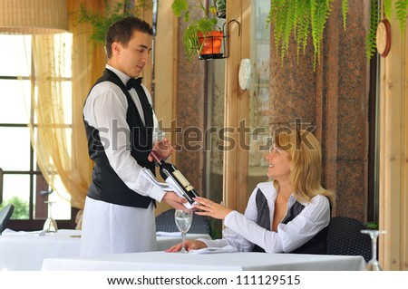 The waiter at the restaurant offers wine visitor