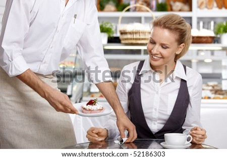 The waiter brings to the visitor the ordered dessert - stock photo