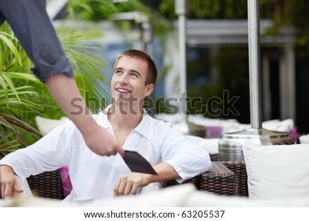 The waiter gives the menu a young man - stock photo